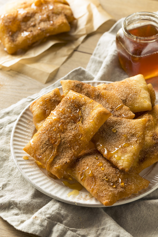 These authentic sopapillas are fried until golden brown, rolled in cinnamon sugar and drizzled with honey.  Eat them while they're hot~  #misshomemade