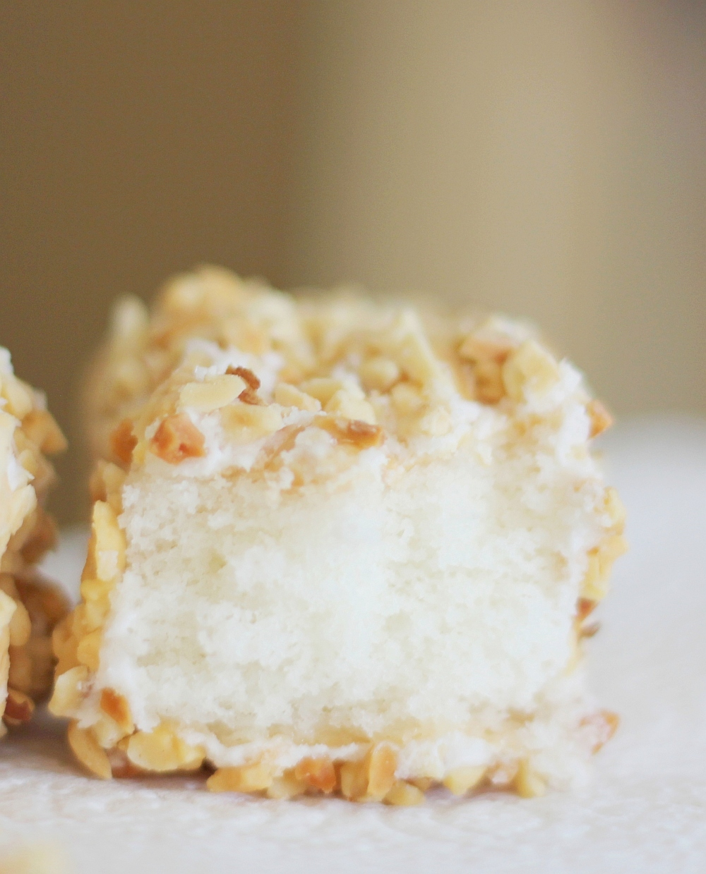 Peanut Squares Recipe - small white cake squares, frosted and rolled in finely chopped nuts. A bakery staple in the Midwest. Heaven. #misshomemade | Thousands of recipes: MissHomemade.com